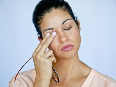 Woman with eyes closed rubbing one eye