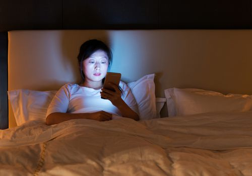 Woman on her phone in bed