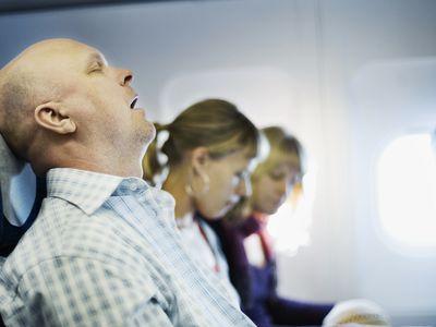 man snoring on airplane