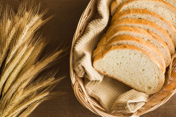 Fresh sliced white bread in the basket on the wooden table in the kitchen. Rustic atmosphere. Healthy eating and lifestyle. Food background.