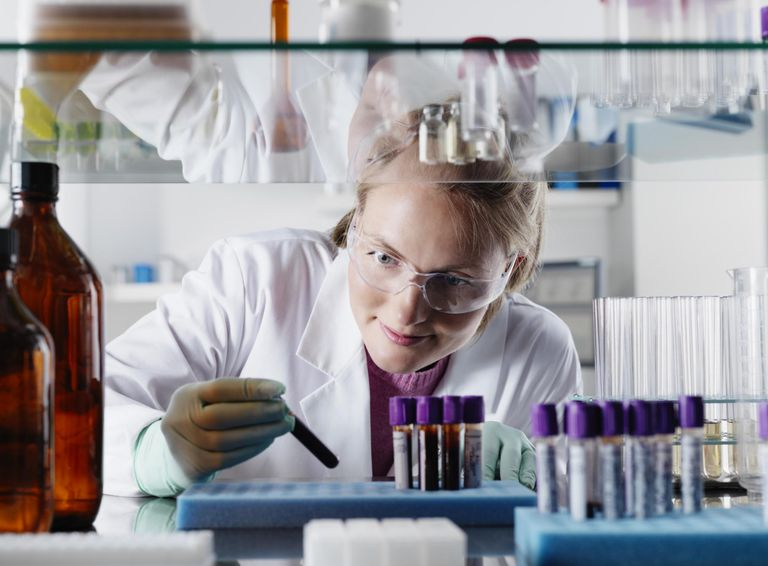 Scientist examining test tubes in lab
