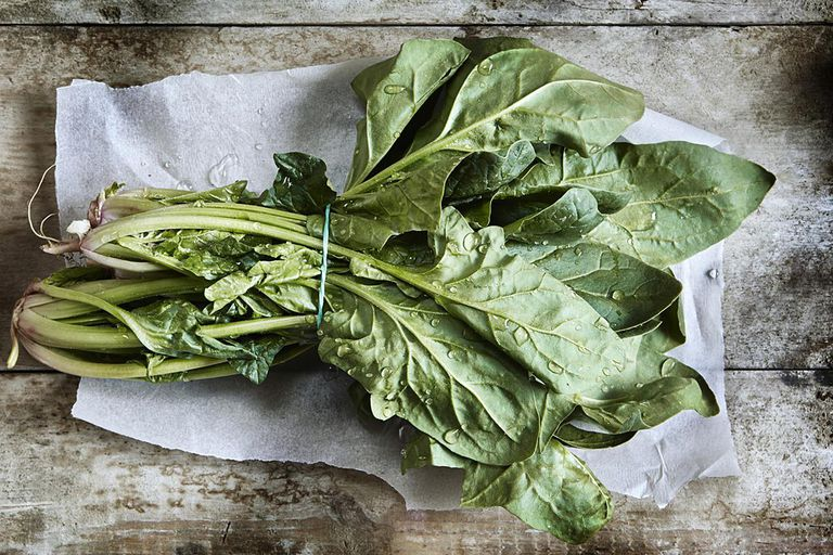 A bunch of uncut spinach on white wrapping paper and a wooden board