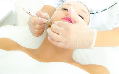 Woman having microdermabrasion treatment done.