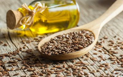 Heap of Flax seeds in a spoon and glass bottle of linseed oil