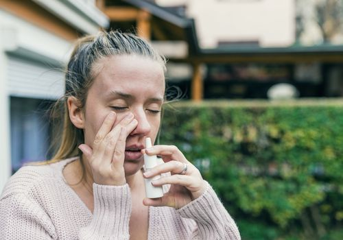 Woman With the Flu using a nasal spray