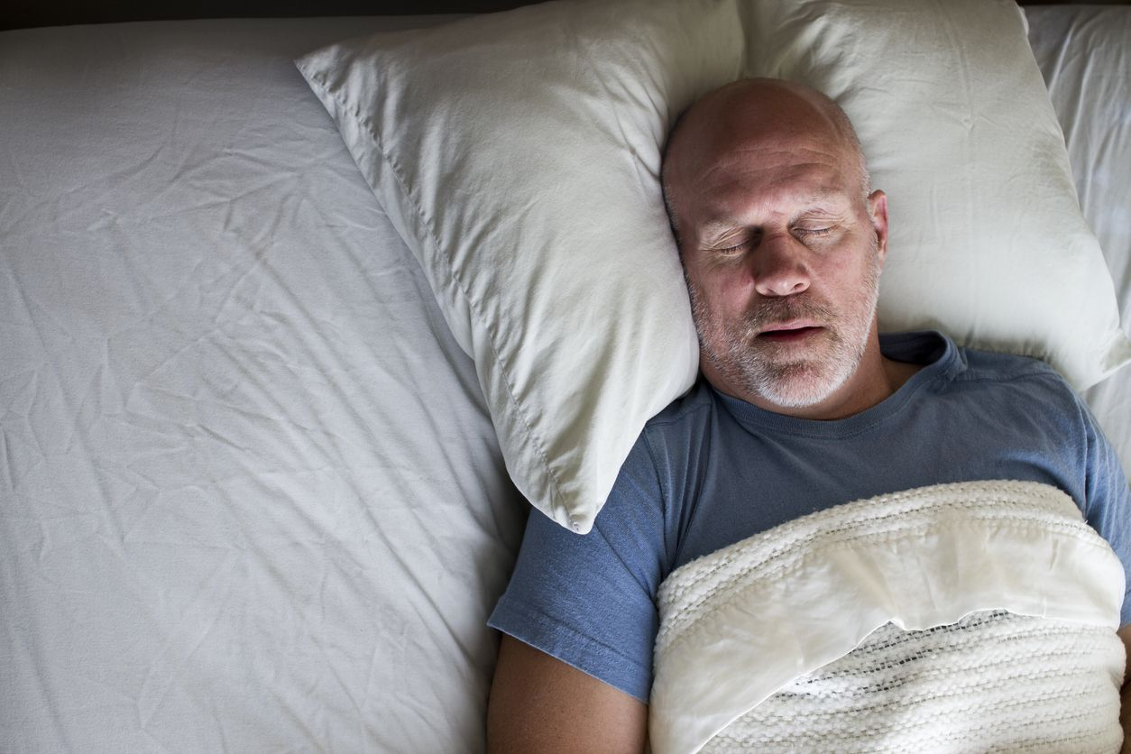 Man laying in bed on back with mouth open