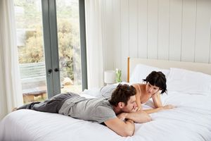 Young couple talking together on their bed in the morning