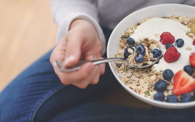 Woman Eating healthy breakfast bowl.
