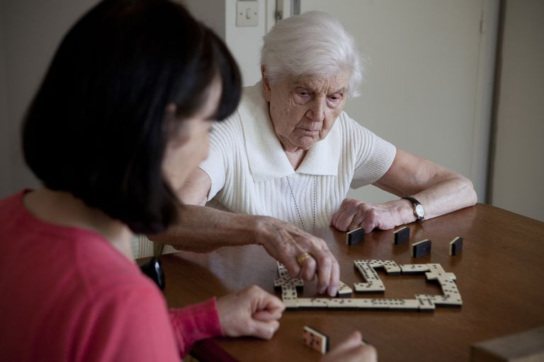 Elderly woman playing game with younger woman.