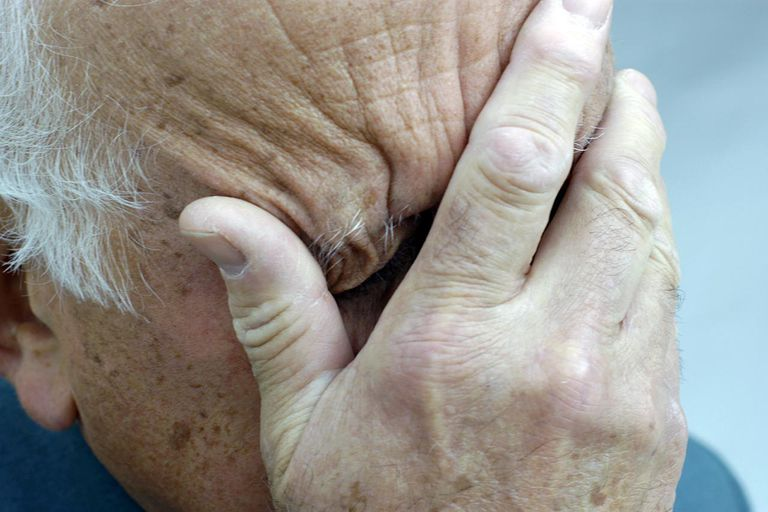 Senior man covering his face with hands