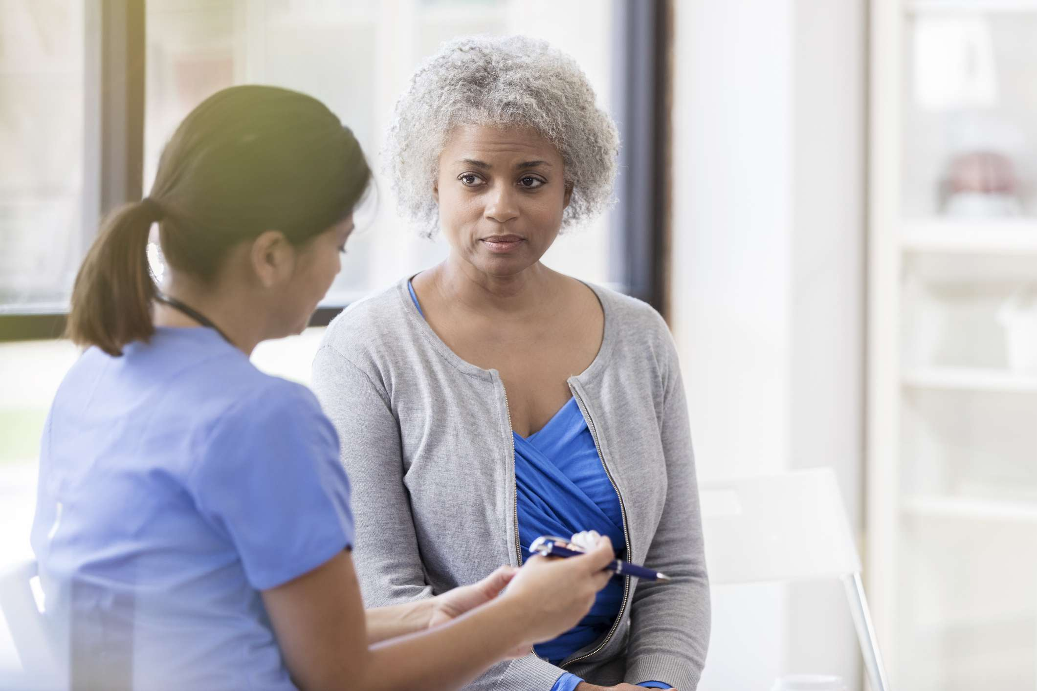 Senior woman listens to doctor's medication instructions
