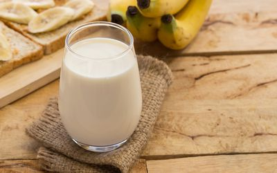 milk on table in front of bananas