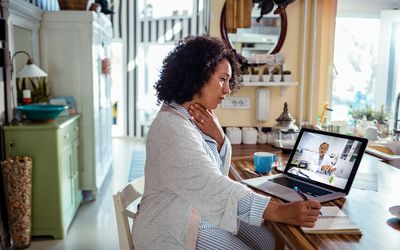 Close up of a mature woman consulting with her doctor online on her laptop
