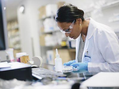Female doctor examining petri dish in a lab