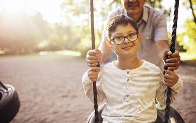 Father swinging disabled son at playground - stock photo