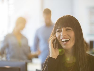 Woman on her phone with healthy teeth smiling