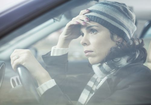 woman driving with a forlorn expression