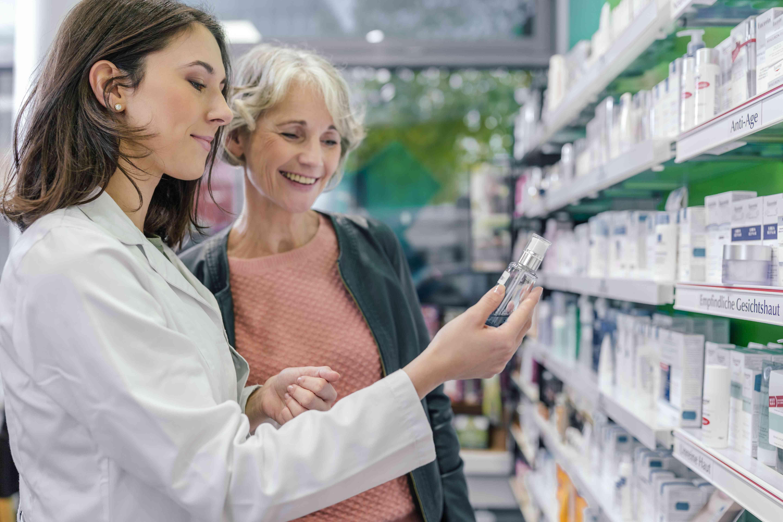 Pharmacist advising customer with cosmetics in pharmacy