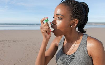 South Africa, Cape Town, young jogger using asthma inhaler on the beach.