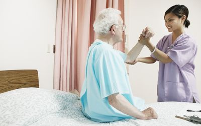 Hospice nurse helping male patient in bed