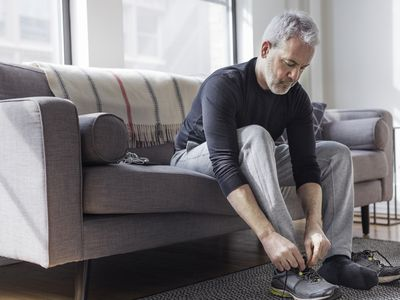 older man on couch lacing up sneakers