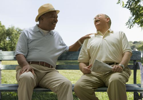Senior men laughing together on a bench