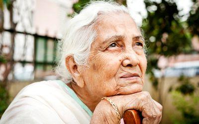 One sad pensive senior Indian woman looking up