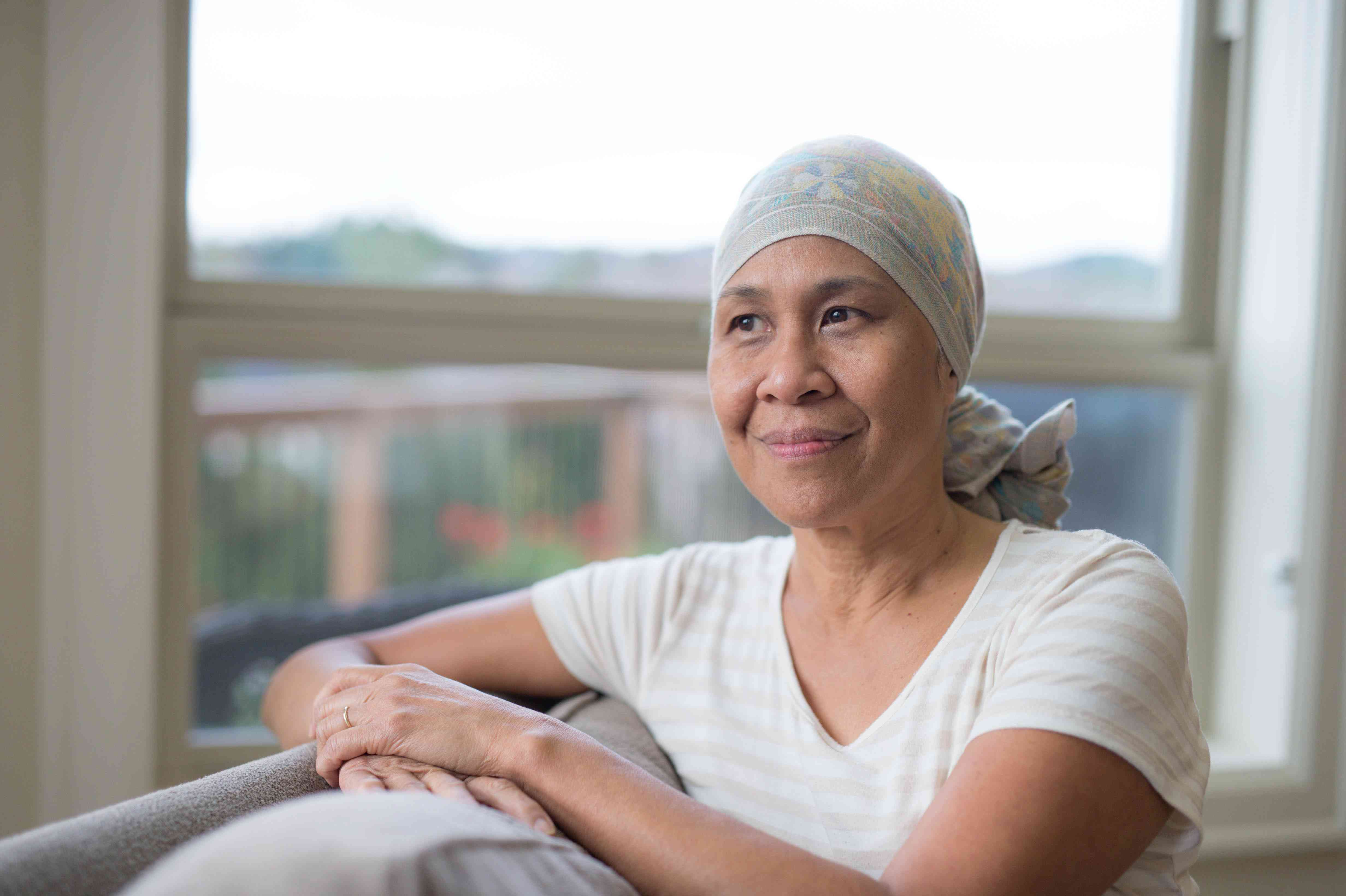 Mature ethnic woman with cancer wearing headwrap on couch