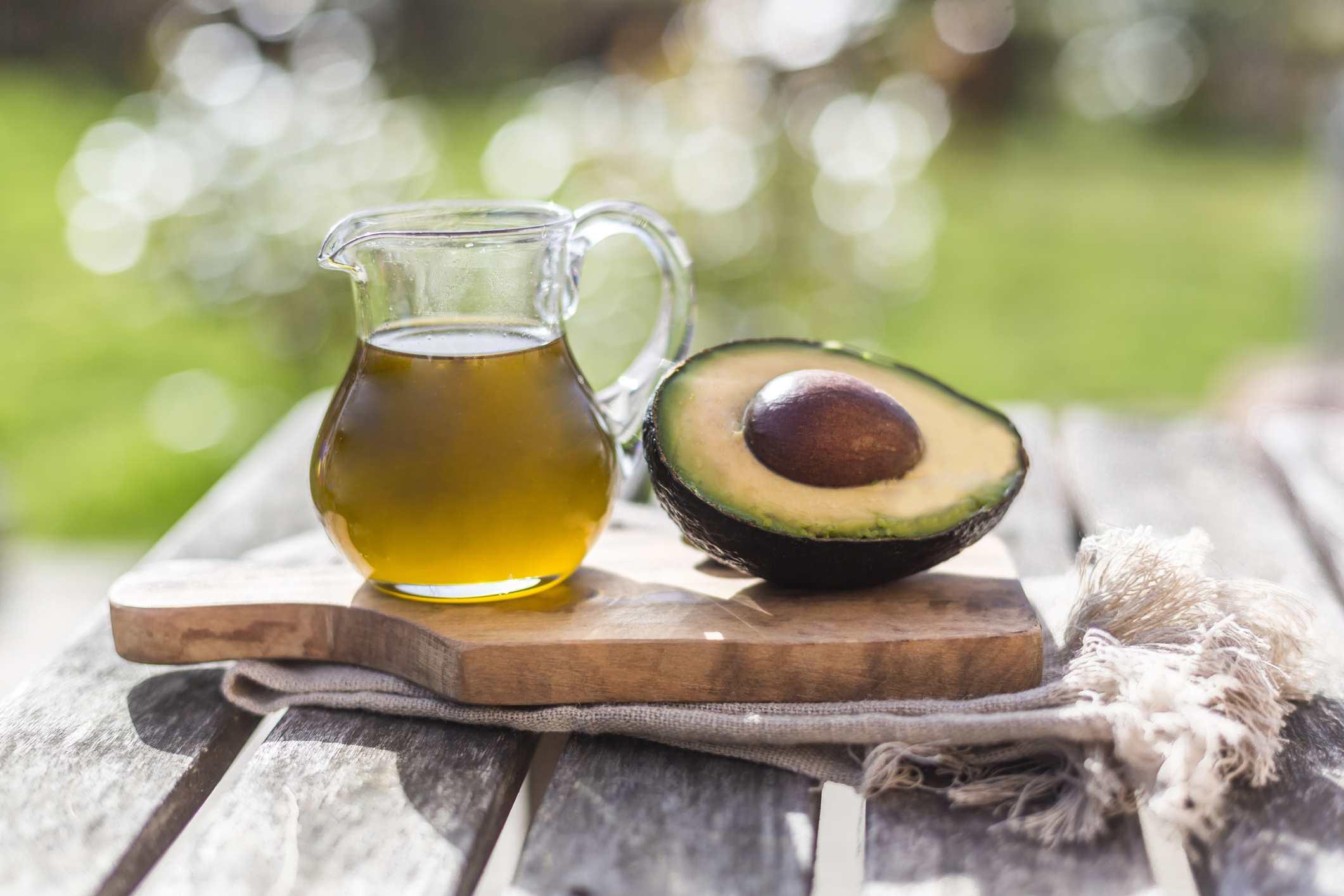 Avocado oil on cutting board next to halved avocado