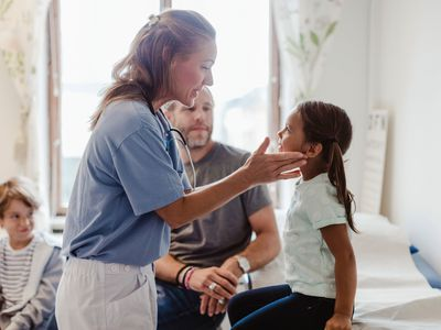 Female nurse examining throat of girl sitting with family at medical room