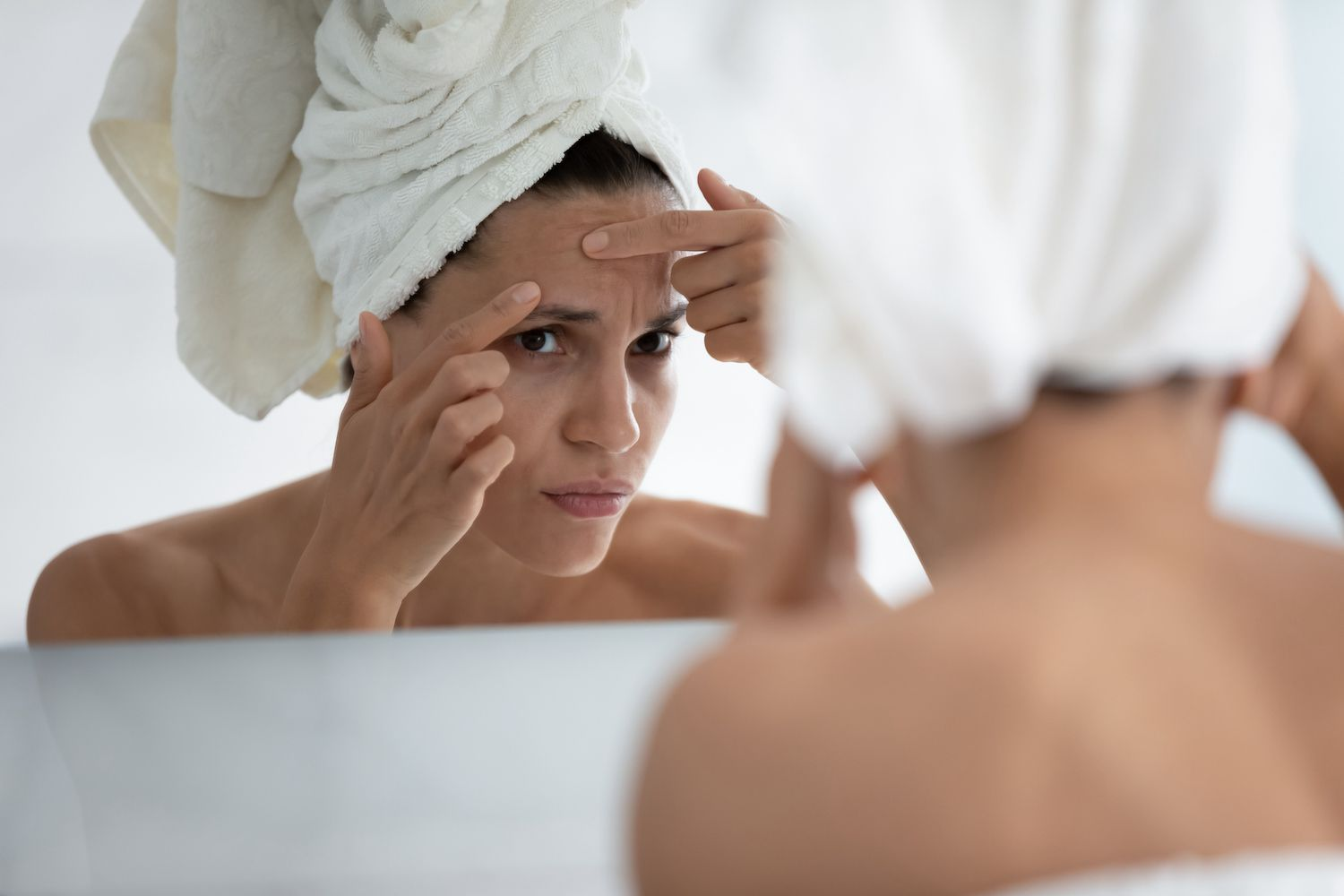 Close up unhappy woman squeeze pimple on forehead