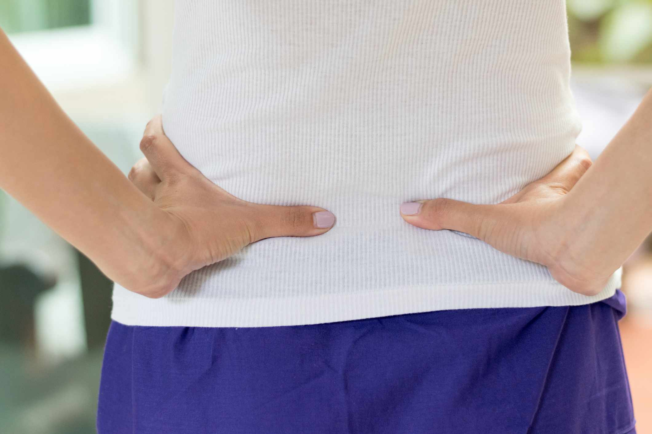 woman with back pain holding her back