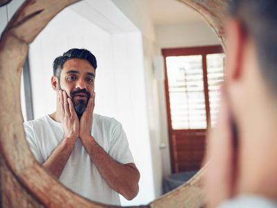 A mature man with dark hair and a beard touching his face with his hands and looking at his reflection in the bathroom mirror.