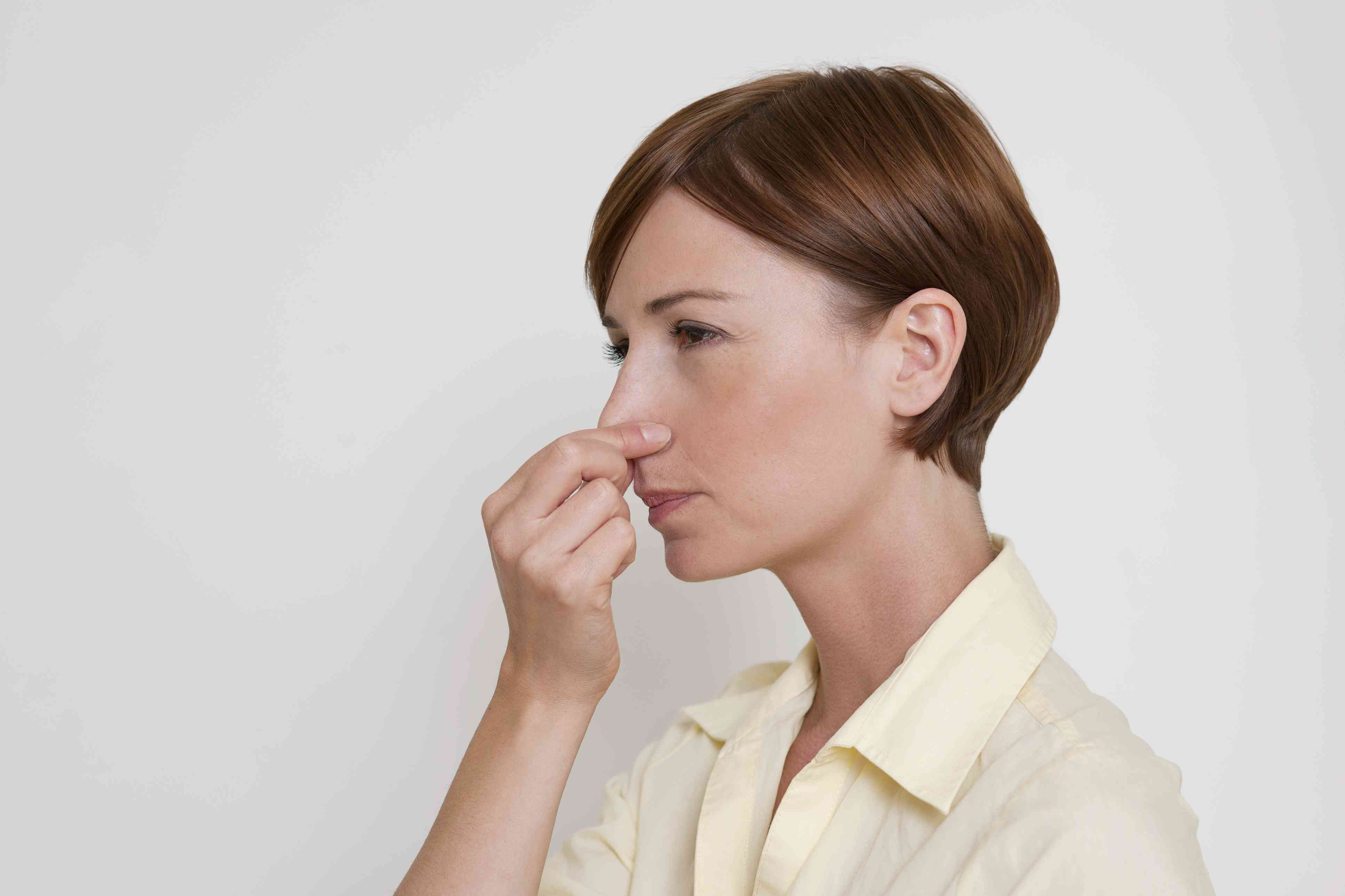 Woman using the Valsalva maneuver by pinching her nose closed