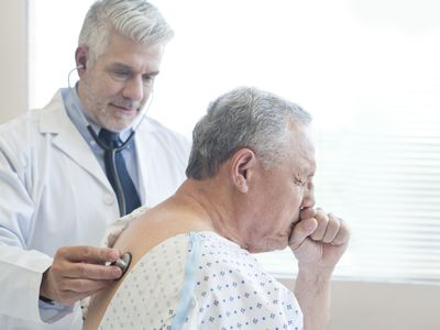 Doctor examining patient in hospital gown.