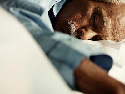 Mature man asleep on bed, close up