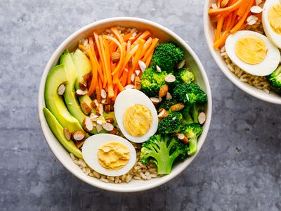 Bowl of brown rice with carrots, eggs, broccoli, avocado, and almonds