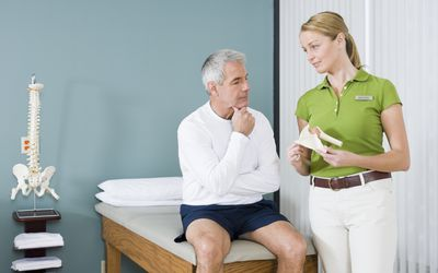 A physical therapist and patient consult.