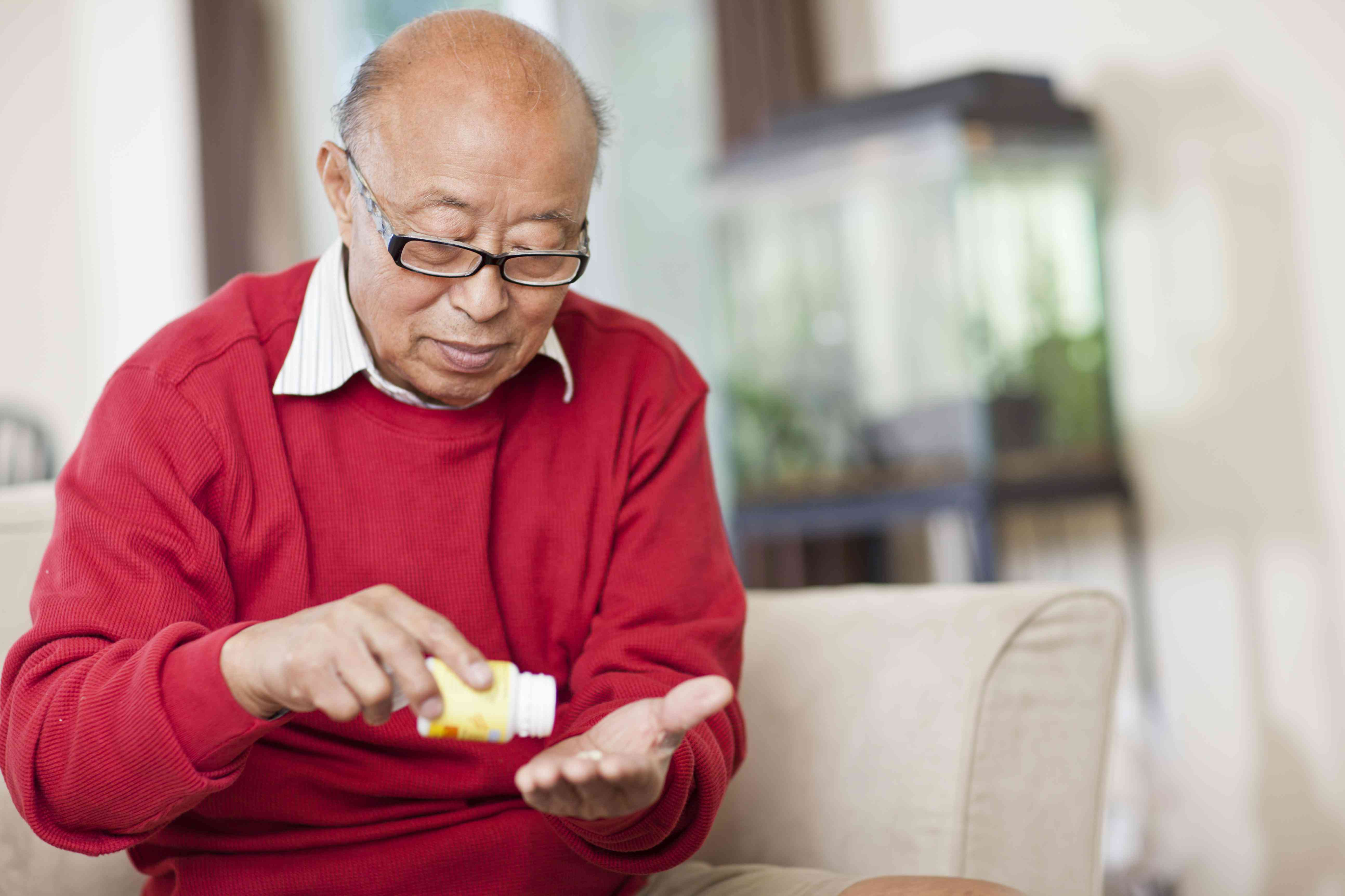 Man sitting on couch taking medication