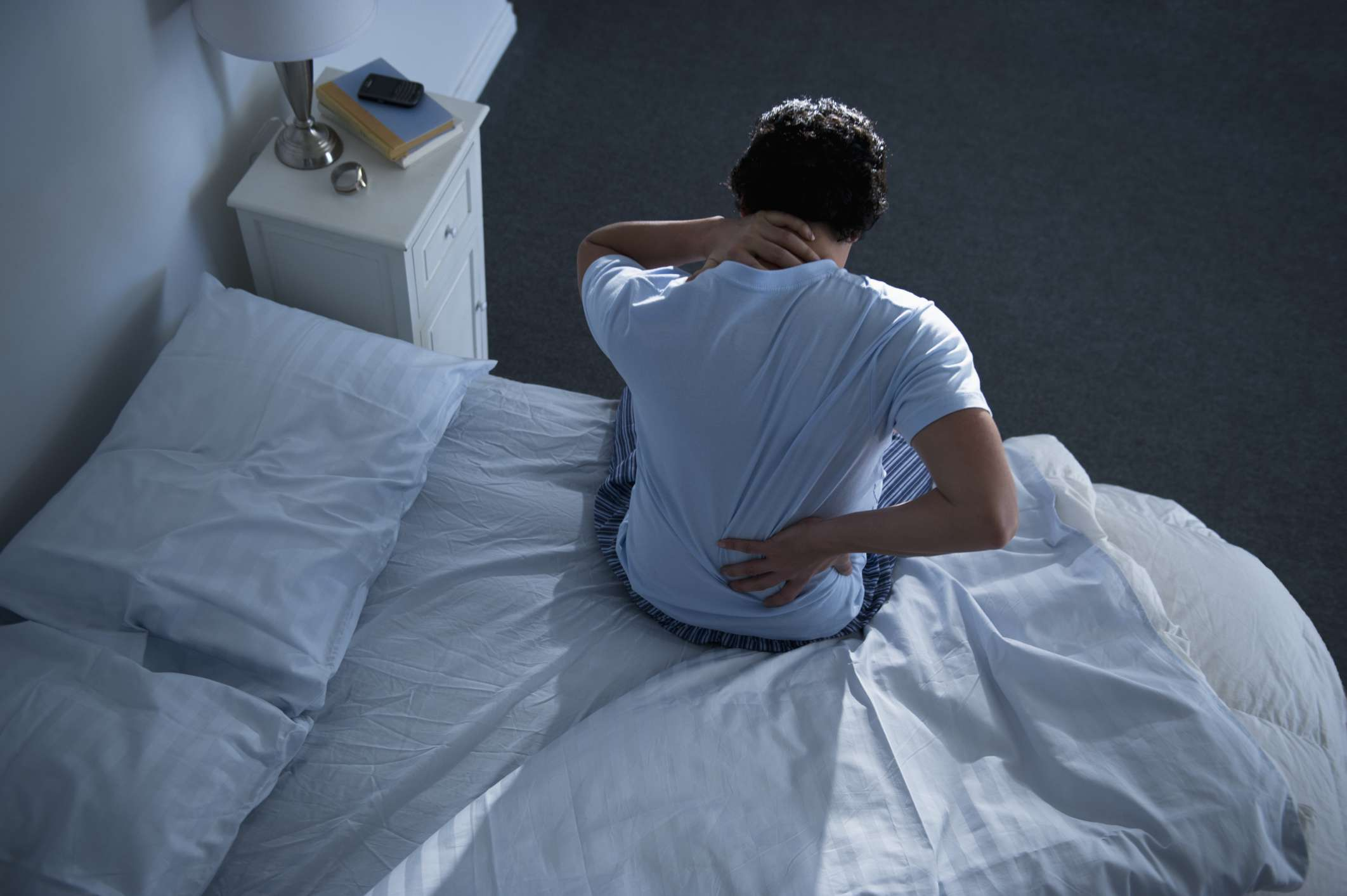 man with back and neck pain on bed