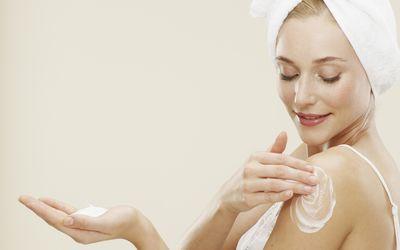 A woman applies moisturizer to her arm.