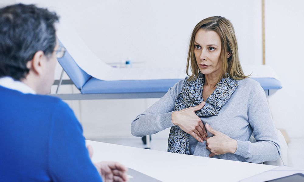 A woman shows signs of heartburn.