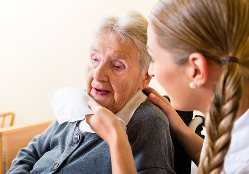 Older woman drooling while nurse wipes chin