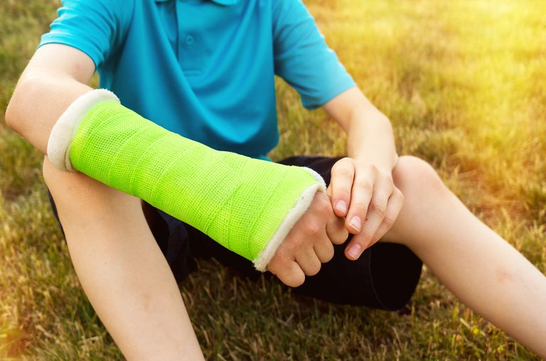 Boy sitting in the grass with a neon green cast on his arm