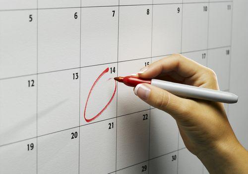 Woman writing on a calendar.
