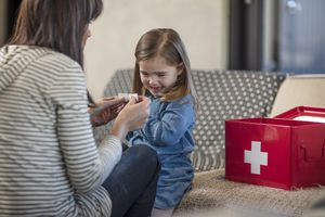 Woman bandaging daughters finger from home first aid kit