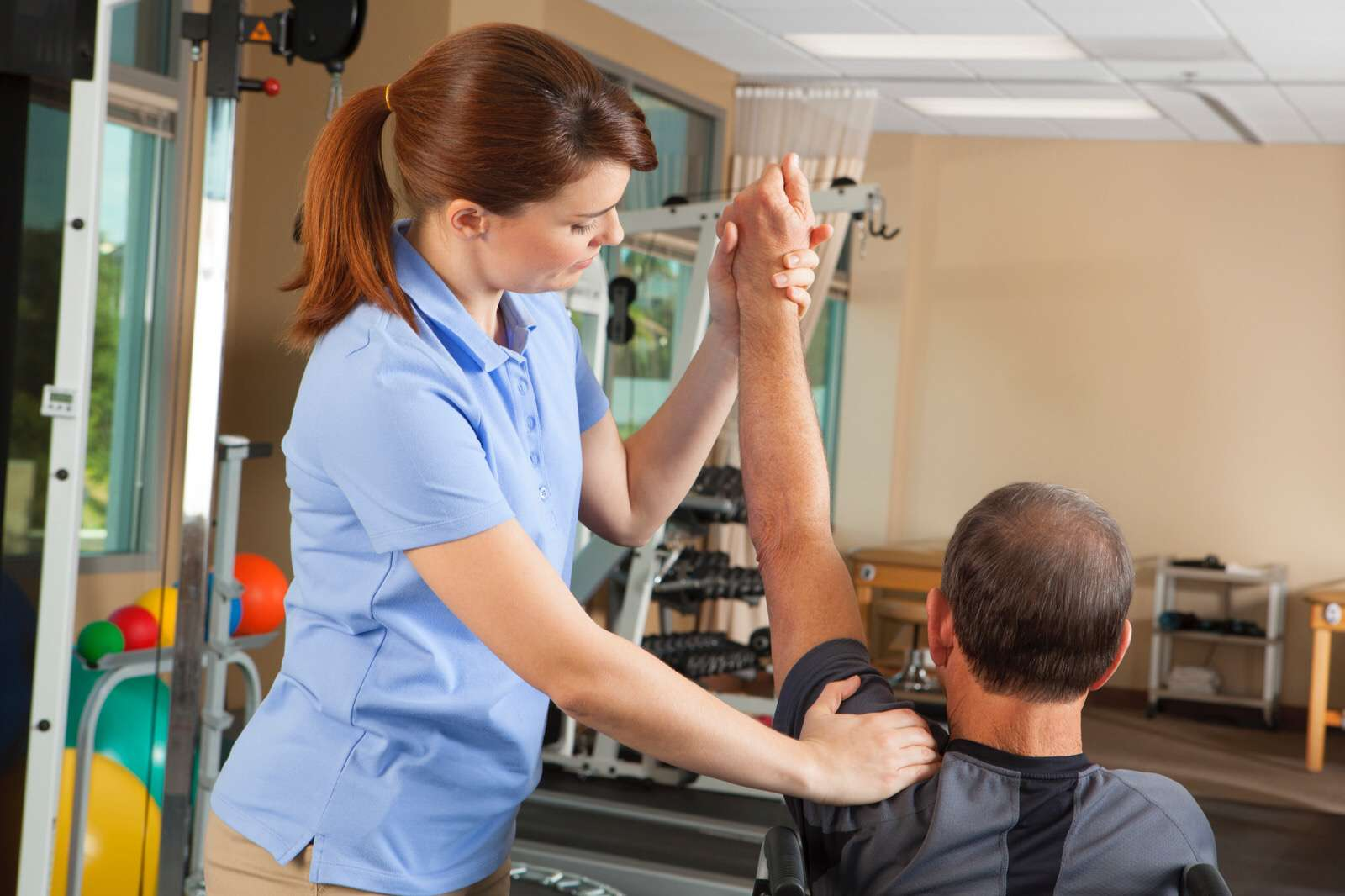 Physical therapist performing shoulder exercises with a patient.
