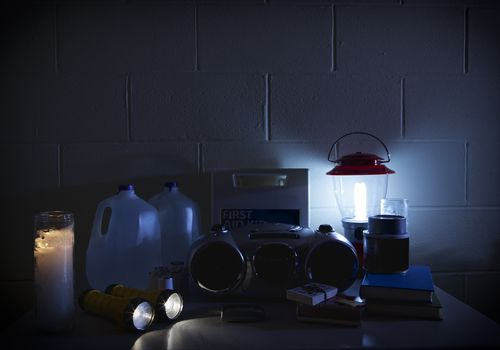 A photo of equipment for use during a power outage like bottles of water, candles, and flashlights.