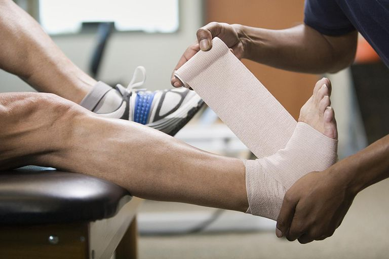 Physical therapist wrapping mature man's foot in bandage, side view