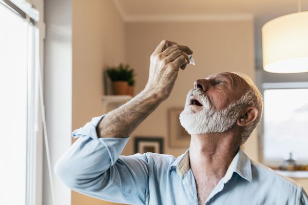 Man using eye drops